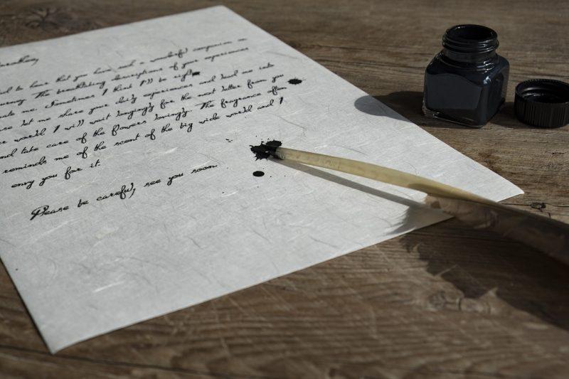 白い紙にインクで英語の筆記体の文章を書いている