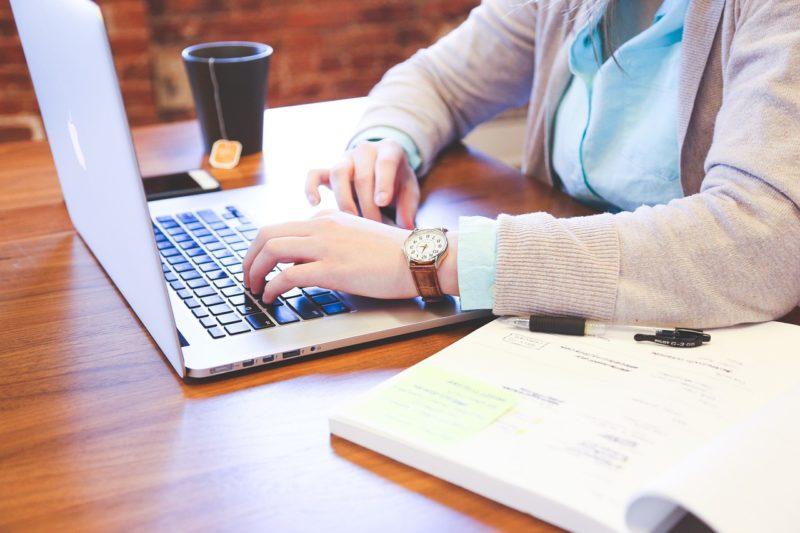 机の上にあるノートパソコンと教科書とティーパックが入ったコップ