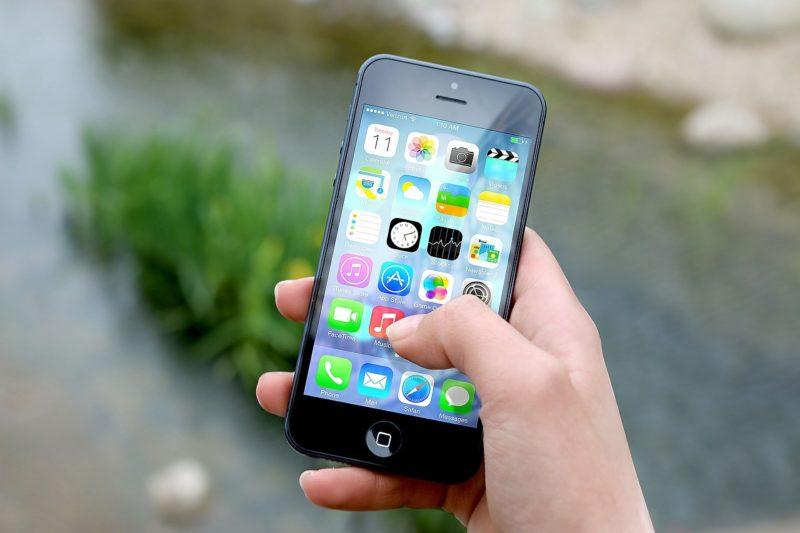 スマートフォン本体と数多くのアプリのアイコン